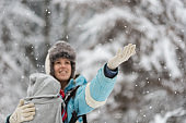 Young mother with her baby in a carrier catching snowflakes
