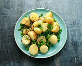 Warm vegetarian new baby potato salad with petit pois peas, Dijon mustard and capers dressing, served with fresh dill