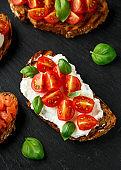 Bruschetta with ricotta cheese, basil, cherry tomato on rustic stone board