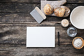 Blank paper ready for written recipe next to homemade bread and ingredients