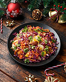 Christmas Red Cabbage, carrots, apples and pecan nuts Salad with decoration, gifts, green tree branch on wooden rustic table