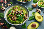Vegan garlic mushroom pasta with spinach and avocado pesto drizzled with sesame seeds and roasted pine nuts