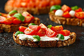 Bruschetta with ricotta cheese, basil, cherry tomato on rustic table