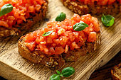 Tomato bruschetta seasoned with basil on a rustic wooden board
