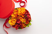 Festive composition with beautiful flowers and berries in red round box