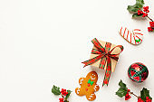 Christmas background with gingerbread cookies, gift boxes and branches of holly