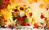 Autumn bouquet of beautiful flowers and berries in a pumpkin on wooden white table.