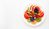 Delicious healthy salad of fresh fruits, berries and edible flowers on white plate.