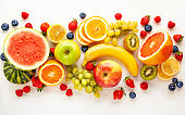 Assorted fresh fruits and berries on white background.
