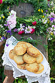 Shortbread cookies with blue cheese and sesame seeds and a wreath of wildflowers on a wooden bench. Rustic style.