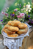 Shortbread cookies with blue cheese and sesame seeds and a wreath of wildflowers on a summer terrace. Rustic style.