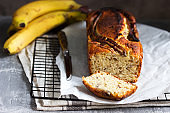 Banana muffin with candied ginger and raisins and bananas on a gray background.