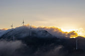High in the mountains are wind turbines at sunrise and sunset and a sea of clouds