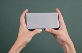 Hands holding mobile phone with blank screen horizontally
