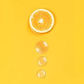 Orange slice and three round drops liquid gel on an orange background Vitamin C medical concept Flat lay style.