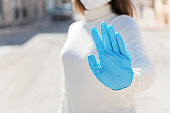 Stay at home. Covid-19 quarantine. A girl in protective mask and gloves blocks Corona virus. Social distance