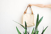 Hand holding linen bag  on wall background .