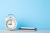 White alarm clock, planner with pen on wooden table at light blue wall background. Planning time concept. Closeup. Empty place for text. Front view.