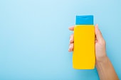 Young woman hand holding yellow tube of sunscreen on light blue table background. Pastel color. Care about skin protection in hot summer. Empty place for text or logo. Closeup. Top down view.