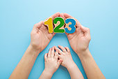 Young adult mother hands showing colorful wooden numbers to baby on light blue table background. Pastel color. Time to learning. Point of view shot. Closeup. Top down view.
