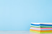Stack of colorful rags on shelf at pastel blue wall. Towels for different surfaces cleaning in kitchen, bathroom and other rooms or towels for face and hands wiping. Empty place for text. Front view.
