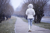 Young woman in white warm clothes and boots slowly walking through alley of trees in winter. Snowing time. Cold atmosphere. Hooded girl. Back view.