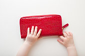 Baby hands touching red leather wallet on light gray table background. Infant exploring mother things. Closeup. Point of view shot. Top down view.