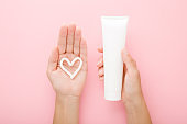 Heart shape created from cream on young woman palm. Hand holding white tube. Point of view shot. Light pink table background. Pastel color. Care about clean and soft body skin. Closeup. Top down view.