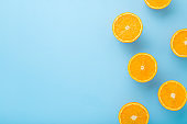 Bright halves of oranges. Fresh fruits. Empty place for text on light blue table background. Pastel color. Closeup. Top down view.