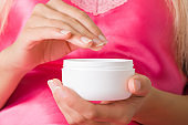 Young adult woman hand holding opened white cream jar. Care about clean and soft body skin. Daily beauty product. Closeup. Front view.