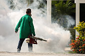 Man pesting gardens to fight the Dengue and Yellow fever mosquito in Brazil. Bug fumigation