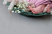 Feet of the newborn baby. pink color. mother's day. little girl in pink bodysuit with white flowers gypsophila