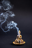Incense cone burning with smoke on the dark background