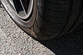 Close up of a punctured flat tire on the asphalt.