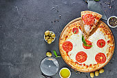 Italian pizza and ingredients for cooking on a black concrete background. Tomatoes, olives, basil and spices. Sliced triangle of pizza. Copy space for text