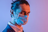 Portrait of a male businessman in a medical mask in dramatic neon light. Crisis for business during the pandemic