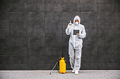 Man in virus protective suit and mask looking and typing on tablet, disinfecting buildings of coronavirus with the sprayer. Infection prevention and control of epidemic. World pandemic.