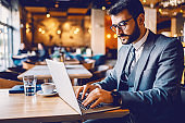 Hardworking caucasian bearded employee sitting in suit with eyeglasses sitting in cafe and typing report on laptop. Hands are on keyboard.