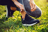 Close up of sportswoman kneeling on lawn and tying shoelace.