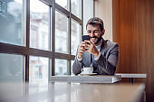 Young cute bearded businessman sitting in coffee shop on coffee break and using smart phone for replying or reading messages.