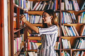 Young gorgeous female student standing next to book shelves and searching for the book for exams.