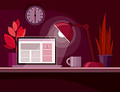 Workplace with a laptop, plant and lamp on the table. Dark red background. Night  room.