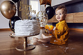 Cute little baby boy sitting on the floor, smashing and playing with his cake on his first birthday.