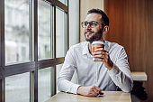 Young handsome bearded elegant man sitting in cafeteria and drinking fresh morning coffee from disposable cup.