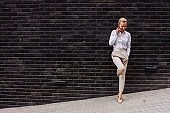 Full length of gorgeous smiling cheerful blond businesswoman leaning on the wall and chatting on the phone.