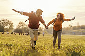 Young happy couple in love holding hands and running in nature. It's a beautiful sunny autumn day. Freedom.