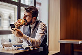 Hungry businessman sitting on lunch break in fast food restaurant, eating cheese burger and using smart phone.