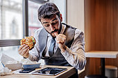 Hungry man in suit sitting in fast food restaurant on lunch break, eating cheese burger and reading news on tablet.