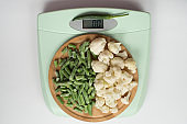 green beans, pepper, cauliflower blooms on a wooden tray on the scales. healthy, dietary food. balanced diet