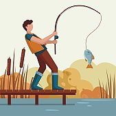 A man caught a fish on the lake on a wooden pier.
